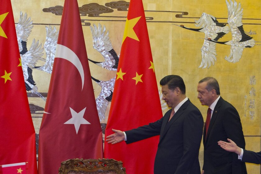 Chinese President Xi Jinping, left, shows the way for Turkey's President Recep Tayyip Erdogan as they attend a signing ceremony at the Great Hall of the People in Beijing, Wednesday, July 29, 2015. (AP Photo/Ng Han Guan, Pool)