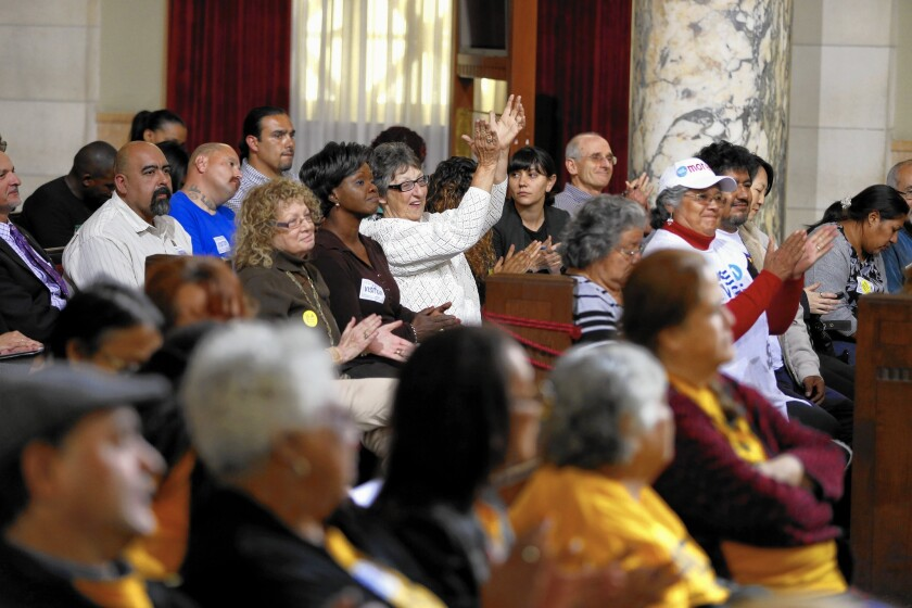 Supporters of a minimum wage increase in Los Angeles applaud a speaker during a City Council committee hearing at City Hall on May 13.