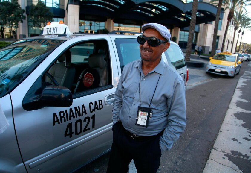 """SAN DIEGO, CA-SEPTEMBER 25, 2015: Taxi driver Gulab Muhammadi proudly displays the 4021 medallion on the side of his cab. Muhammadi is among the first wave of newly permitted drivers under the city's new loosened policy. """"I am very happy,"""" said Muhammadi. """"I don't have to pay the owner anymore because now I am the owner."""" (Misael Virgen / San Diego Union-Tribune)"""
