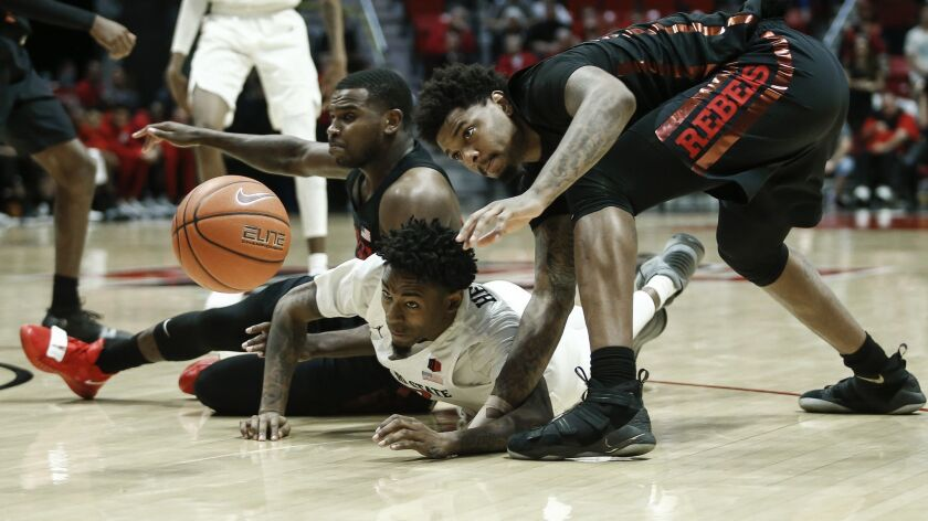 SDSU's Jeremy Hemsley (center), dives for a loose ball with UNLV guard Amauri Hardy (left) and forward Tervell Beck (right) during theirJan. 26 game at Viejas Arena.