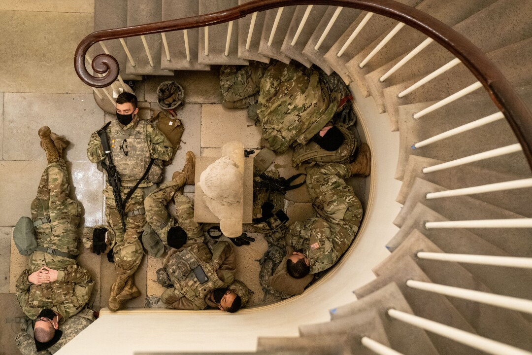 Service members in uniform sleep in an alcove below a curved stair
