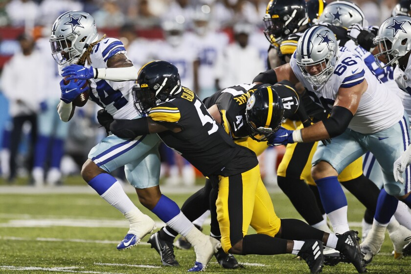 Dallas Cowboys running back Rico Dowdle (34) tries to escape the grasp of Pittsburgh Steelers linebacker Ulysees Gilbert III during the first half of the Pro Football Hall of Fame NFL preseason game Thursday, Aug. 5, 2021, in Canton, Ohio. (AP Photo/Ron Schwane)