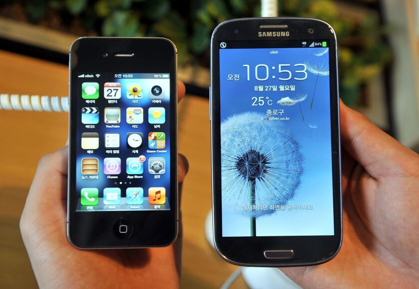 An employee shows an Apple's iPhone 4s, left, and a Samsung's Galaxy S3 at a mobile phone shop in Seoul.
