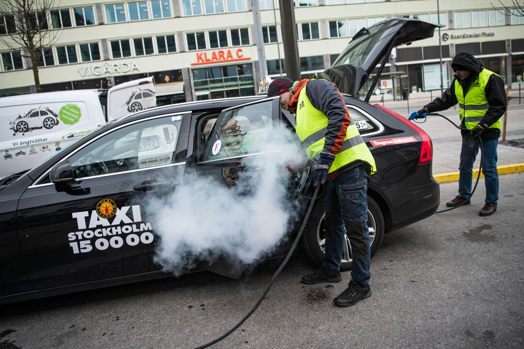 Two men clean and disinfect a taxi in Stockholm on Tuesday.