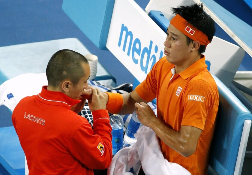 Kei Nishikori of Japan receives treatment from a trainer during his third round match against Guillermo Garcia-Lopez of Spain at the Australian Open tennis championships in Melbourne, Australia, Friday, Jan. 22, 2016.(AP Photo/Vincent Thian)