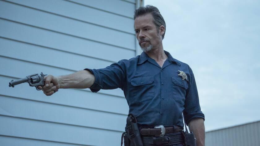 """Guy Pearce as a lawman brandishing a gun in the movie """"Disturbing the Peace."""""""