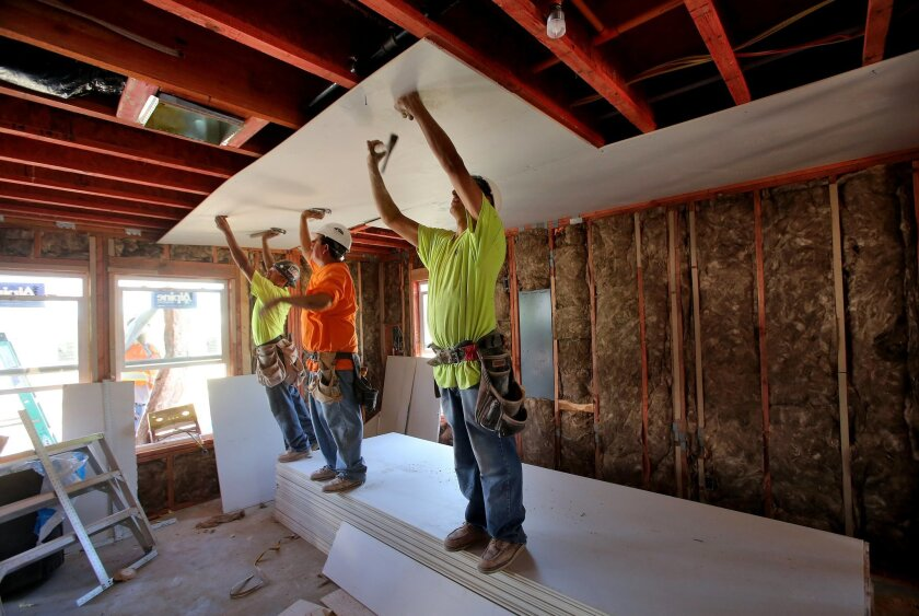 Workers Brian Coln, Ramiro Plascencia and Guillermo Torres team up to install sheet rock on the ceiling of the downstairs floor of this Habitat for Humanity home in the 500 block of N. Elm Street in Escondido on Tuesday. Shea Homes , Sempra Energy, and Emmerson Construction are participating in a f