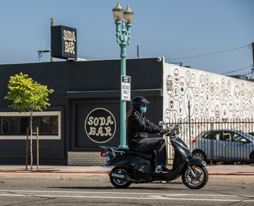 A moped rider wearing a mask drives past Soda Bar in City Heights, one of the many music venues that will be closed for the foreseeable future due to COVID-19 on May 14, 2020 in San Diego, California.