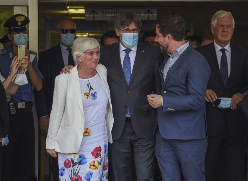 Catalan leader Carles Puigdemont, center, is flanked by European Parliament members Antoni Comin, right, and Clara Ponsati, left, as he leaves the Sassari law court, Italy, Monday, Oct. 4, 2021. Catalonia's former separatist leader Carles Puigdemont walked out of a Sardinian courthouse Monday after a judge delayed a decision on Spain's extradition request and said he was free to travel. First from right is Puigdemont's lawyer in Italy Agostinangelo Marras. (AP Photo/Gloria Calvi)