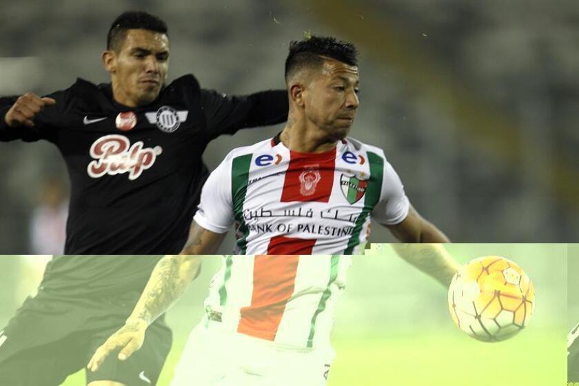 El jugador de Palestino Leonardo Valencia (d) disputa el balón con Sergio Vergara (d). EFE/Archivo