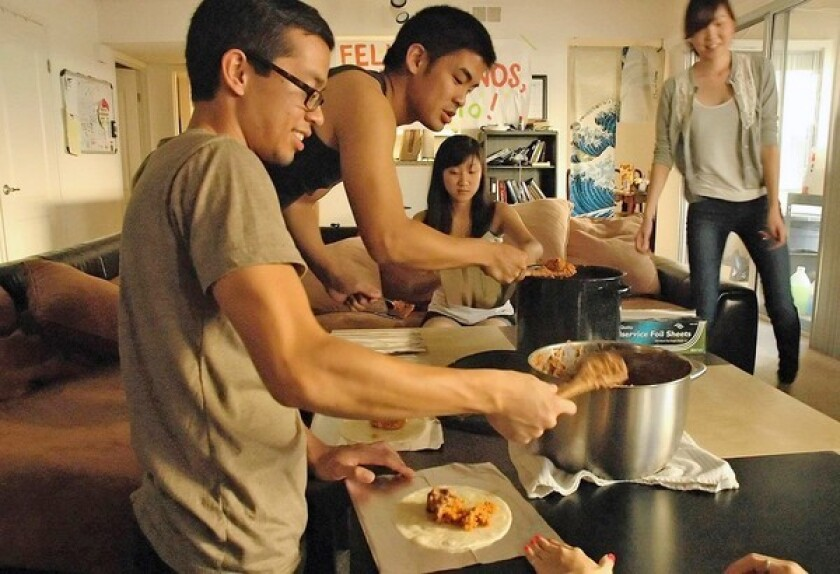 Anthony Singhavong, Nate Fung, Shirley Chang, and Emi Nakamura, left to right, make burritos on the living room table.