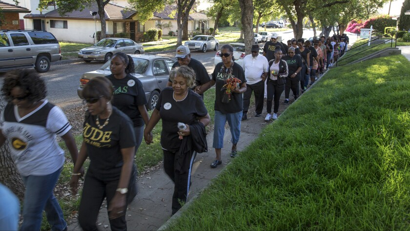 Community members join together for a prayer walk in remembrance of Jason Spears, 12, who was shot to death in March.