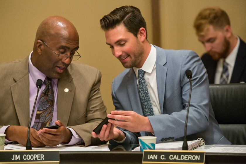 Assemblyman Jim Cooper, left, checks out Assemblyman Ian C. Calderon's cellphone during a hearing session at the Capitol on July 7, 2015.