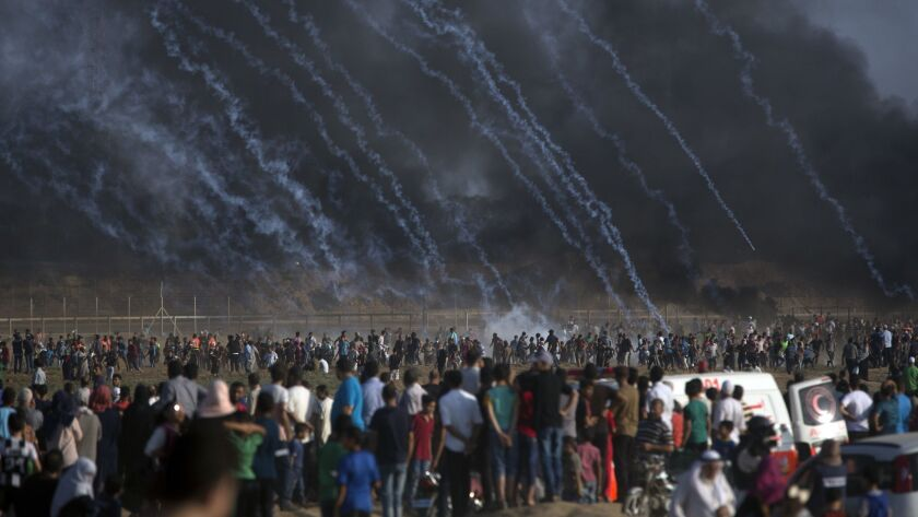 Tear gas canisters fired by Israeli troops rain down on Palestinians during a July 13 protest at the Gaza Strip's border with Israel.