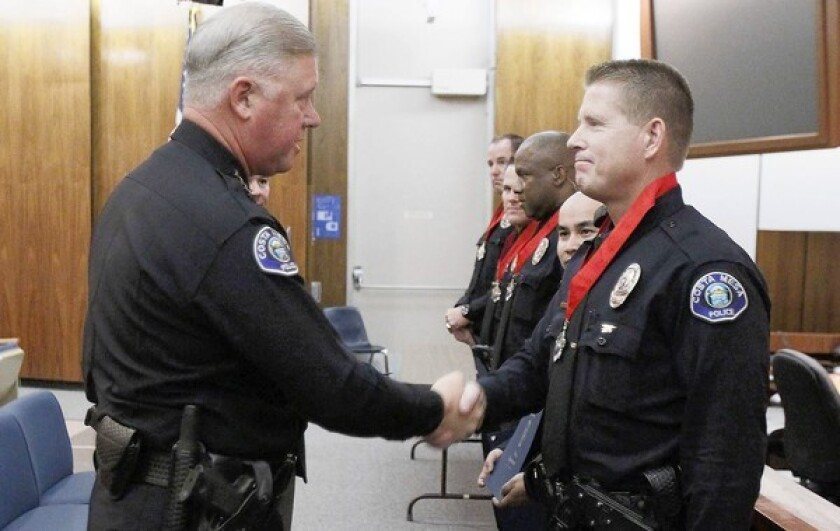 Costa Mesa Chief of Police Tom Gazsi shakes Jon Doezie's hand during a ceremony at Costa Mesa City Hall commending officers' actions in responding to a July 8 shooting where a man allegedly killed his former girlfriend.