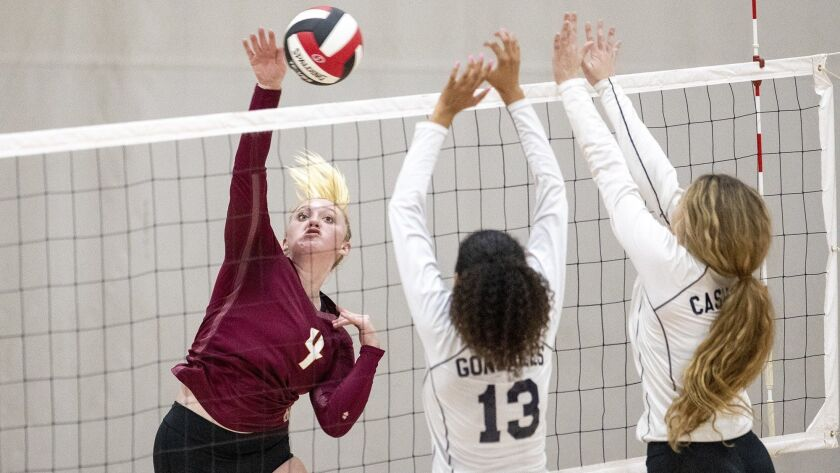 Ocean View's Katelyn Taylor hits into Chatsworth's blockers Rylee Gonzales, center, and Kelli Cashma