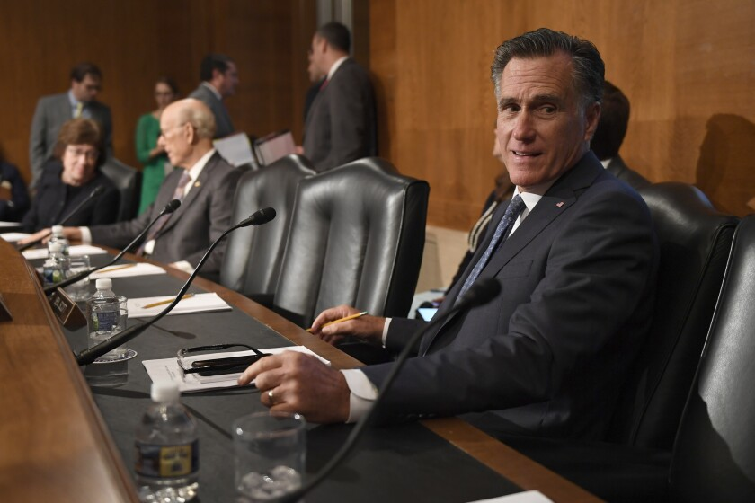 Sen. Mitt Romney, R-Utah, talks with a colleague during a break in an executive session of the Senate Health, Education, Labor and Pensions Committee on Capitol Hill in Washington, Tuesday, Sept. 24, 2019. The committee voted to advance Scalia's nomination to the full Senate for consideration. (AP Photo/Susan Walsh)