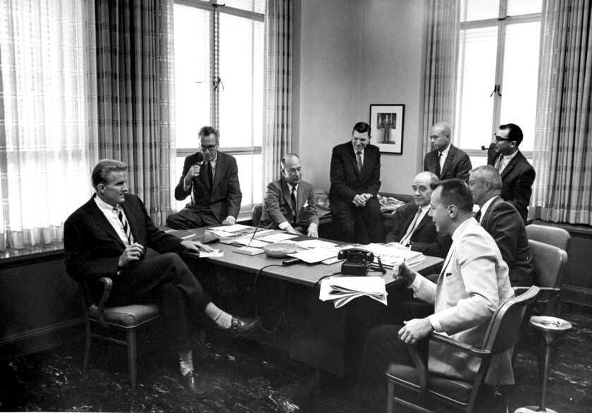 A group of men sit around a desk in an old Los Angeles Times office