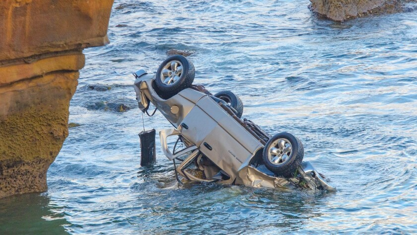 A pickup is upside down in the water after going over the edge at Sunset Cliffs with a man and his two young children inside.