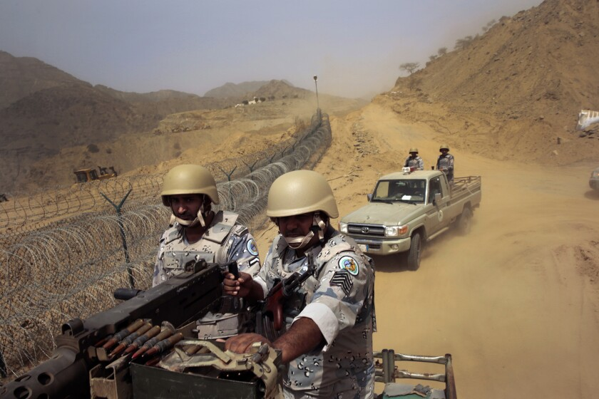 Saudi border guards ride along the rugged border with Yemen near the town of Addayer.
