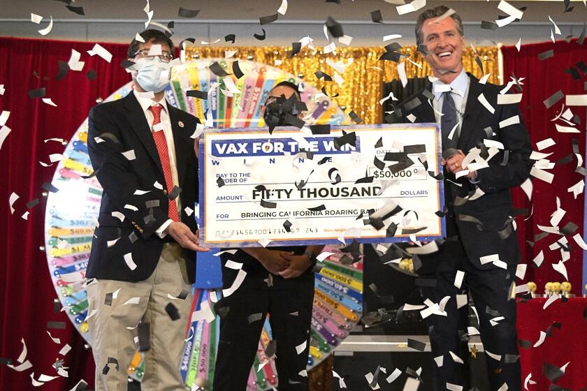 Three men hold a big mock check while confetti rains down on them.