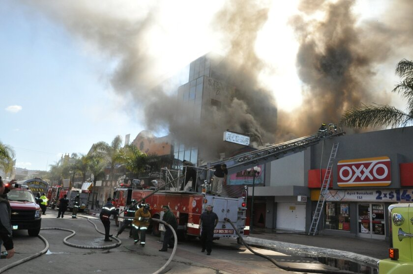 Tijuana firefighters battle a fire Tuesday at the Aloha Bar on Avenida Revolucion. During the 1960s, the bar was popular with rock-and-roll fans from both sides of the border who came to listen to performances by Carlos Santana and Javier Batiz.