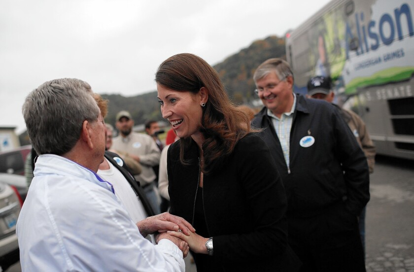Kentucky Democratic Senate challenger Alison Lundergan Grimes greets supporters at a campaign rally. She has been forced to respond to attack ads linking her with President Obama that have been funded largely by a Kentucky coalition not required to disclose its donors.