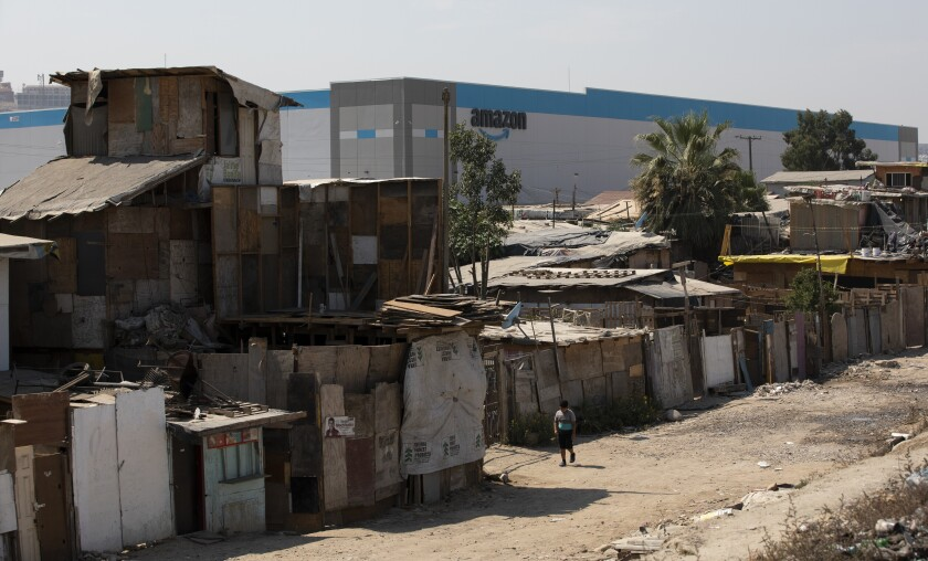 Flimsy homes in front of a big warehouse.