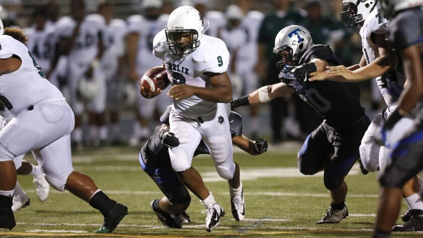 Helix running back Michael Adkins, who scored three touchdowns, charges for yardage against Eastlake.