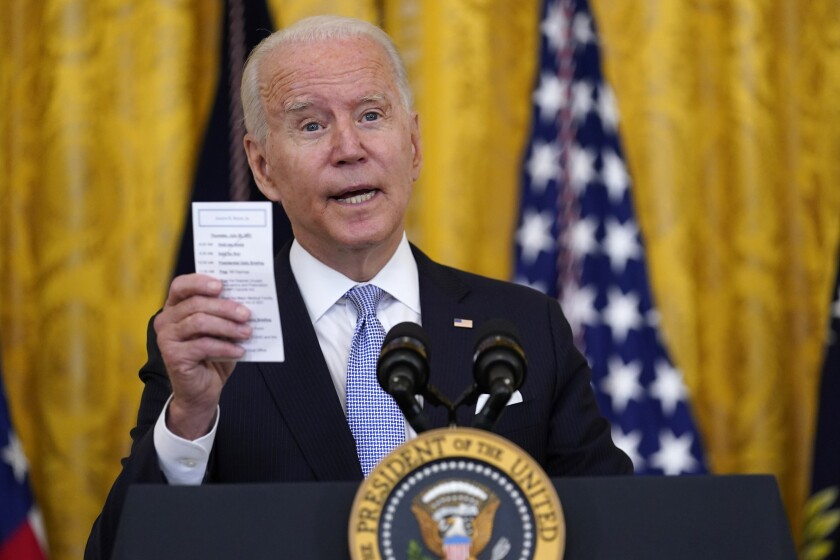 Biden holds up a note card while speaking at a podium at the White House