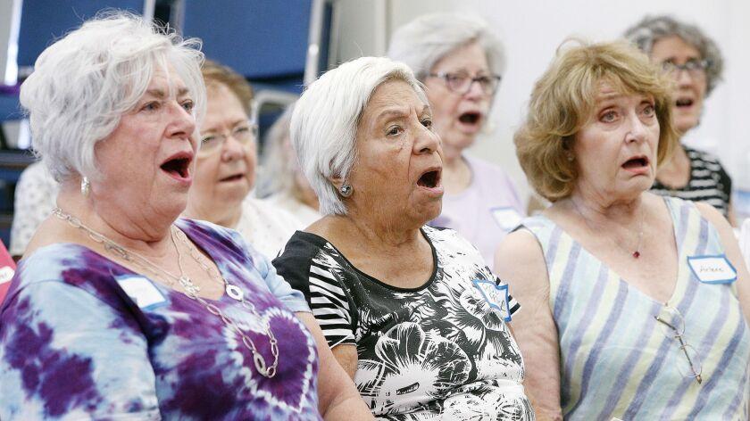 Jeanne Long, Rosa Former, and Arlene Massimino, of the Verdugo Hills Women's Chorus, work on vocal e