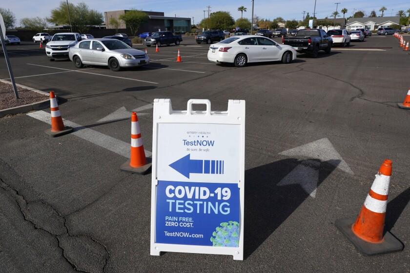 Personas esperan en sus vehículos para hacerse la prueba del COVID-19, en Phoenix, Arizona.