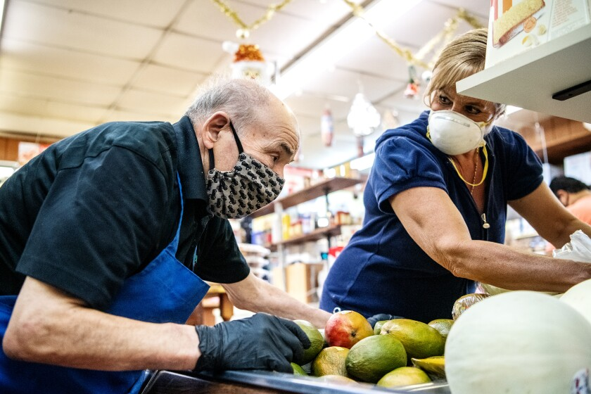 Roma Market owner Rosario Mazzeo helps a customer select some produce.