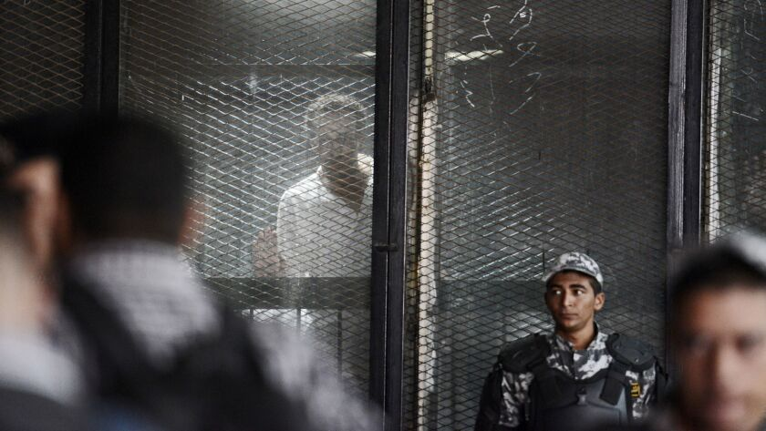 """Photojournalist Mahmoud Abou Zeid is seen behind bars during a court hearing July 28, 2018. He is one of the more than 700 defendants in a political mass trial in Cairo for whom the """"maximum penalty"""" of death by hanging was requested by the prosecution."""