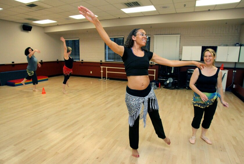 Belly dancing class at the Paul Ecke Family YMCA's dance studio- Instructor Georgia Schmidt leads the class. At right is student Pamela Gran.