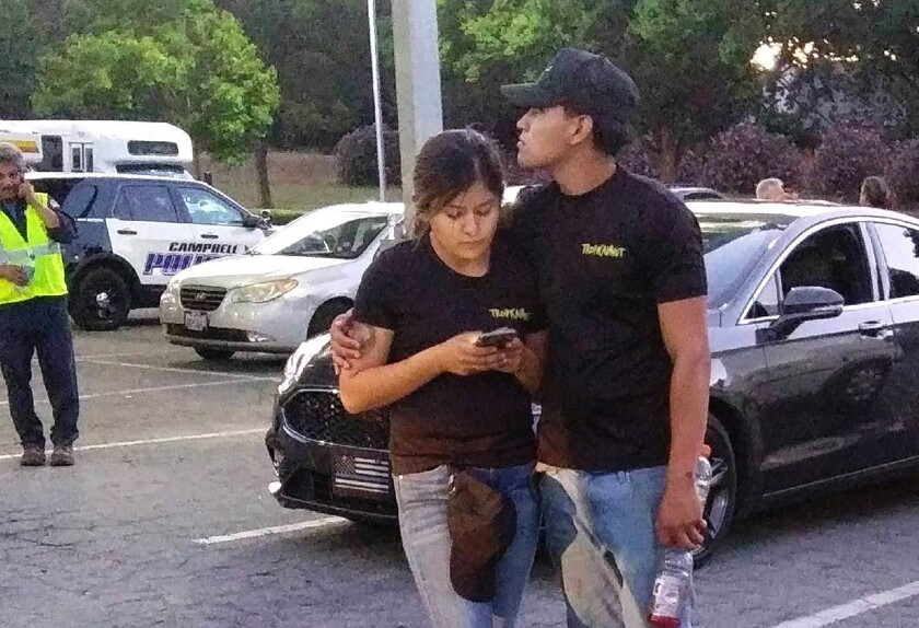 A young couple embrace in a parking lot after a shooting at the Gilroy Garlic Festival.