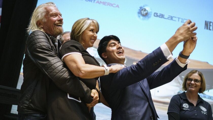 Virgin Galactic founder Richard Branson picks up New Mexico Gov. Michelle Lujan Grisham while company employee Kevin Prieto takes a selfie with them at an event Friday in Santa Fe.