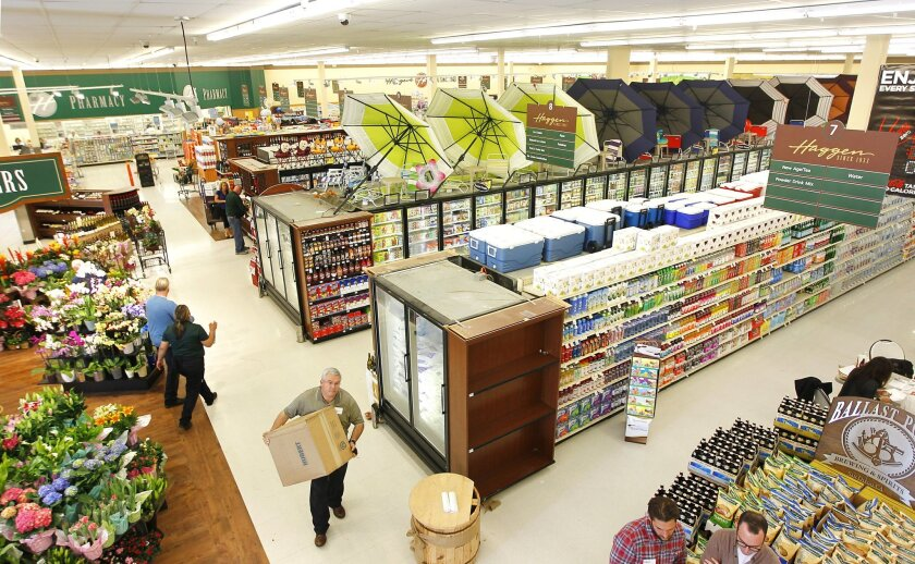 Workers prepare Haggen supermarket for the store's grand opening in Carlsbad Wednesday. The chain plans to open a number of stores in San Diego.