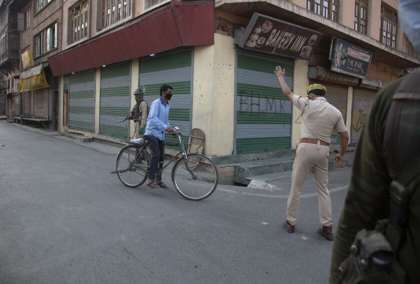 An Indian police officer asks a civilian to take an alternative road as they block traffic in Srinagar, Indian controlled Kashmir, Monday, July 13, 2020. Authorities reimposed lockdown on Monday in parts of Indian-controlled Kashmir, including the region's main city, following surge in coronavirus cases. (AP Photo/Mukhtar Khan)