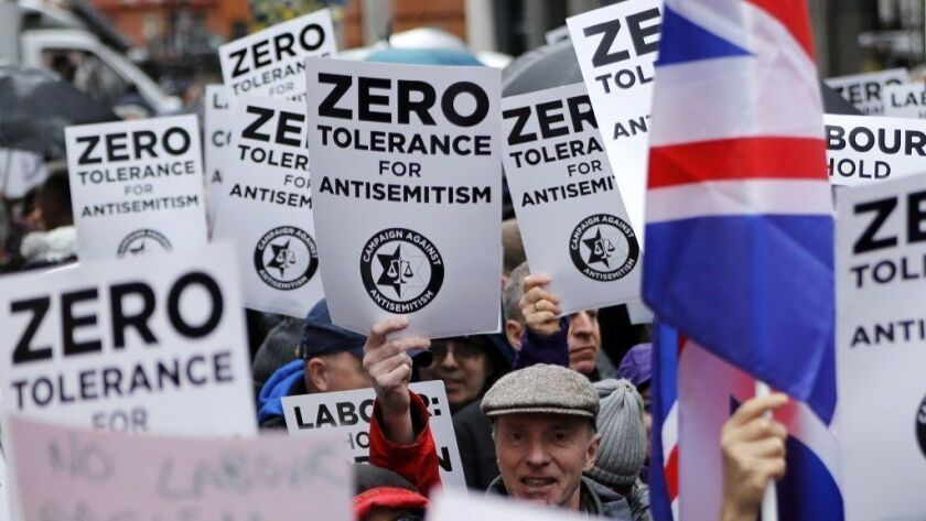 People hold up placards during a demonstration in London organized by the Campaign Against Anti-Semitism on April 8.