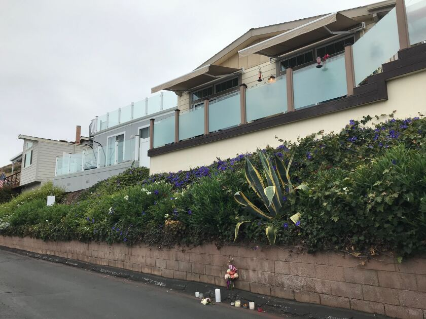Vase of flowers and candles on the street below a landscaped slope leading up to home with retaining wall.