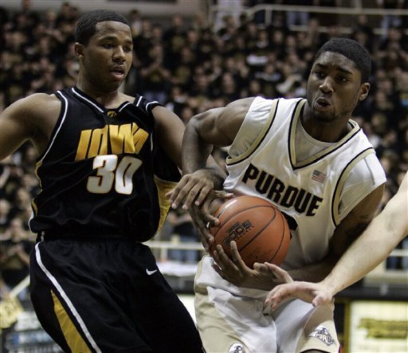 Purdue guard E'Twaun Moore, right, and Iowa guard Jeff Peterson get tangled as Moore drives the lane in the second half of an NCAA college basketball game in West Lafayette, Ind., Sunday, Jan. 18, 2009. Purdue defeated Iowa 75-53. (AP Photo/Michael Conroy)