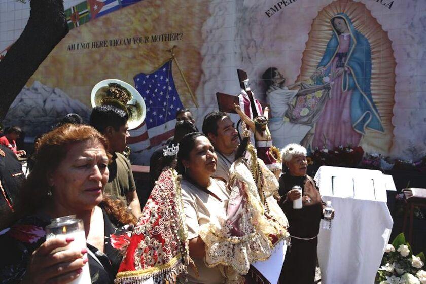 Migrantes hispanos rezan por las víctimas de balaceras en California, El Paso, Texas, y Ohio frente a la iglesia Nuestra Señora la Reina de los Ángeles en Los Ángeles.
