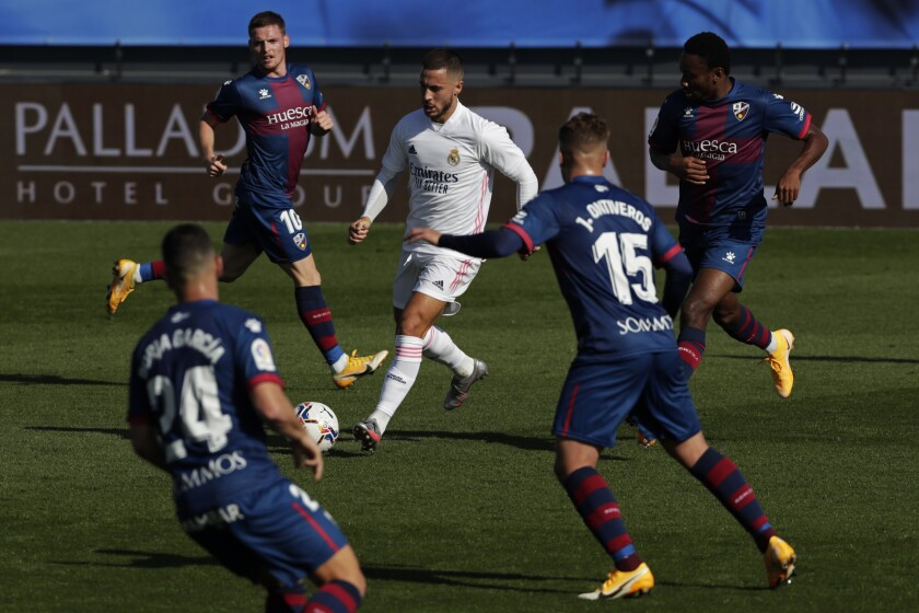Real Madrid's Eden Hazard, center, runs with the ball next to Huesca defenders during the Spanish La Liga soccer match between Real Madrid and Huesca at Alfredo di Stefano stadium in Madrid, Spain, Saturday, Oct. 31, 2020. (AP Photo/Manu Fernandez)