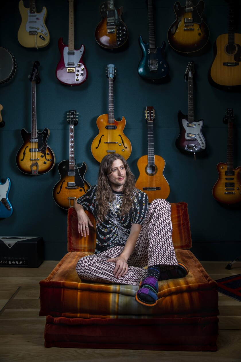 Ludwig Göransson in his Glendale recording studio, sitting in front of a wall of guitars.