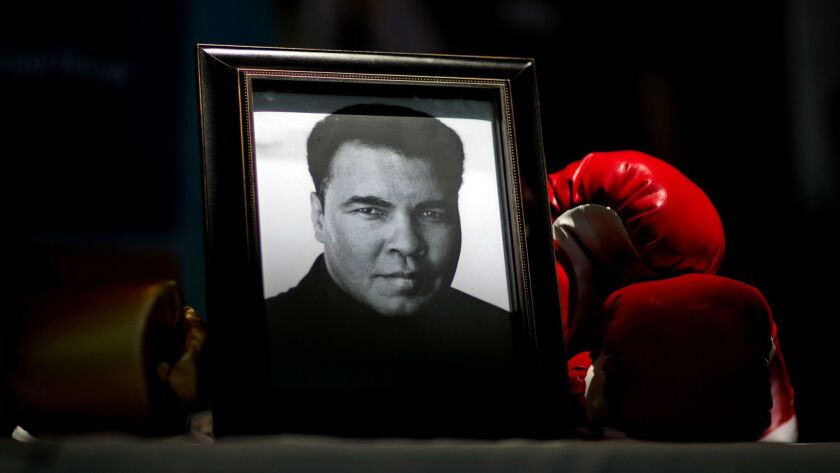 """A portrait of Muhammad Ali is displayed next to a pair of boxing gloves at the """"I Am Ali Festival"""" in Louisville."""