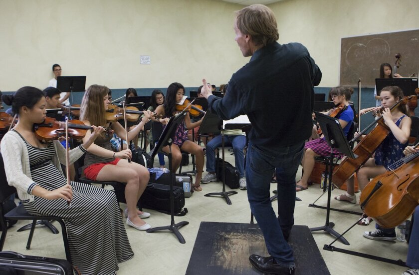 Jeff Edmons conducts members of the International Youth Symphony in rehearsal, including Flora Li (far left) and Mattea Anderes (second from left). Crissy Pascual/Infinite Media Works