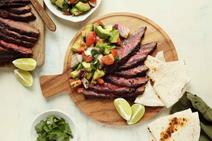Grilled steak with guacamole salad is laid out on a wooden plate, garnished with slices of lemon and lime