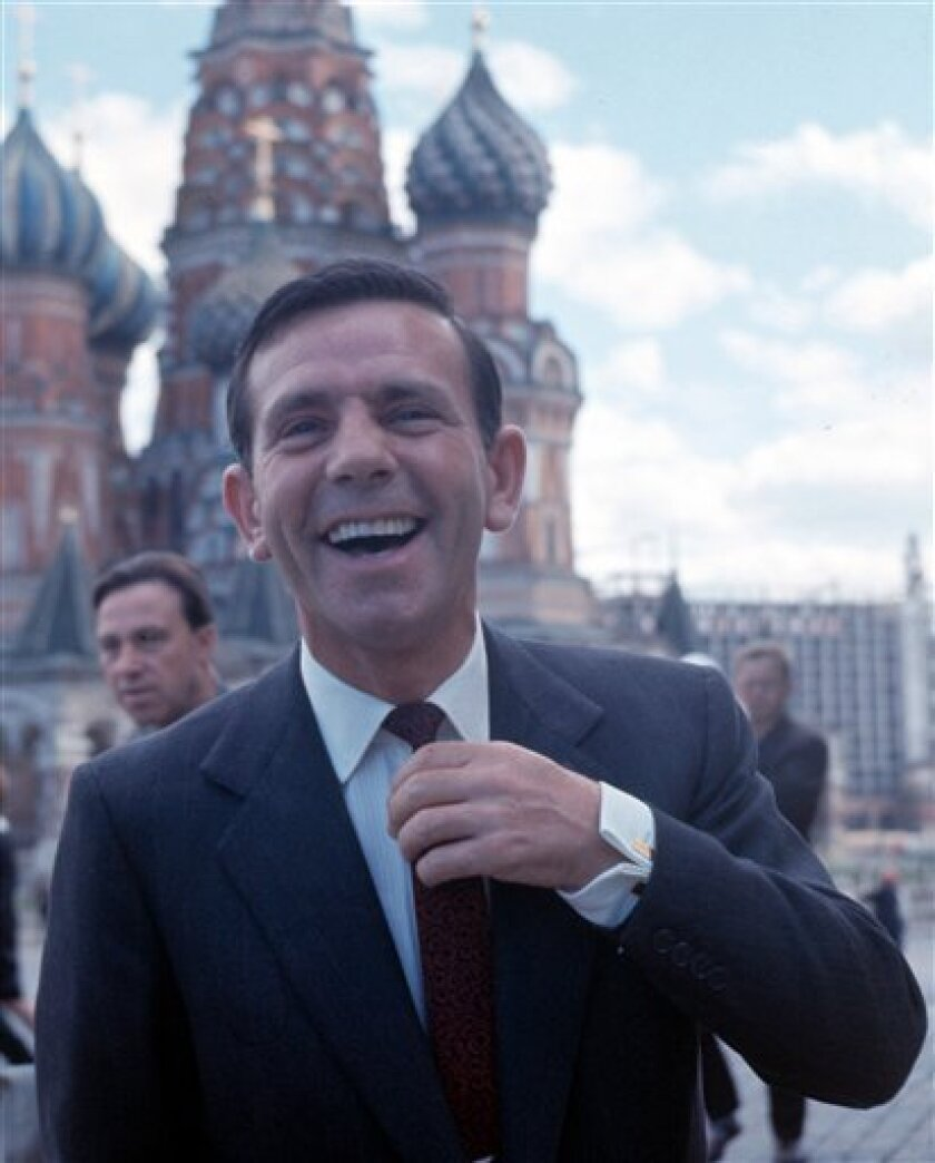 FILE - British actor and comedian Norman Wisdom laughs with the photographer, in Red Square, Moscow, USSR, in this July 18, 1965 file photo. In the background is St. Basil's Cathedral. The British Broadcasting Corporation reported late Monday Oct 4 2010 that the veteran funny man, star of stage, screen and TV, had died, aged 95. (AP Photo, file)