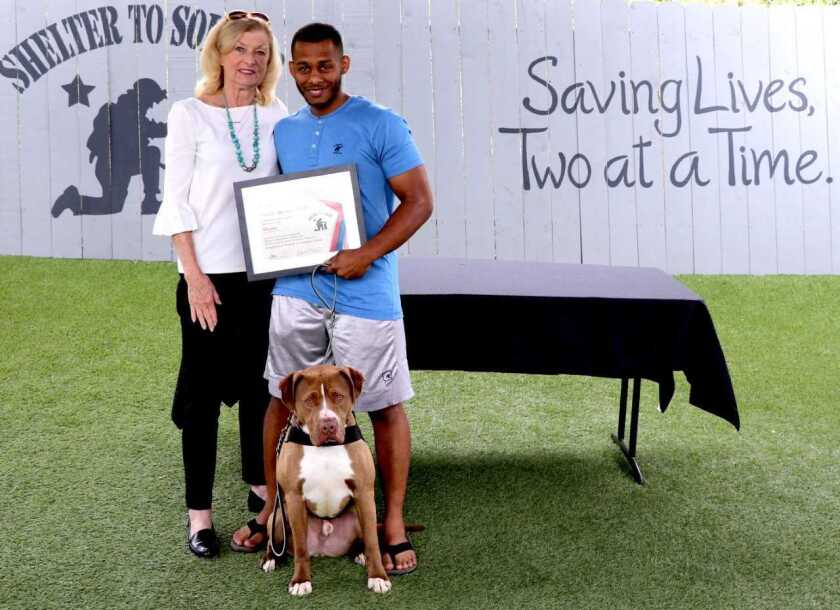 Oceanside-based nonprofit Shelter to Soldier received a $30,000 grant from the Petco Foundation to support its rescue dog and veteran program that trains service dogs for veterans suffering from post-traumatic stress disorder, traumatic brain injury and other similar injuries. Recently, Moose, a pit bull mix adopted from the San Diego Department of Animal Services Bonita Shelter (and one of the Petco Foundation's sponsored service dogs), graduated with Marine veteran Jaimie McAfee at the program's headquarters. From left: Peggy Hilliar from the Petco Foundation with McAfee and Moose. Visit sheltertosoldier.org.